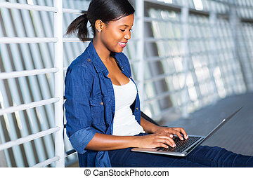 african american woman using laptop computer - happy african...