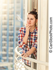 beautiful woman smoking cigarette on balcony - Toned...