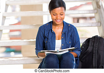 african american university student reading a book - smart...