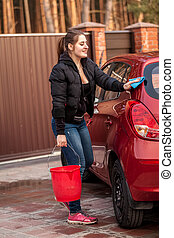 young woman washing her small red car - Beautiful young...