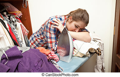 exhausted woman ironing big pile of clothes - Photo of...