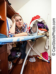 depressed housewife leaning against ironing board - Closeup...