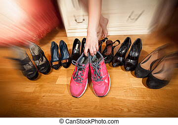 Closeup photo of active woman picking sneakers rather than...