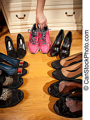 woman choosing sneakers rather than hugh heeled shoes -...