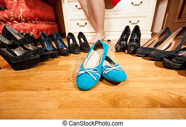 blue ballet flats standing among black high heel shoes -...