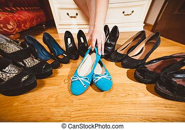 woman picking ballet flats rather than high heels - Closeup...