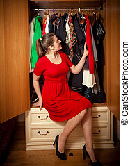 woman choosing what clothes to wear at wardrobe - Beautiful...