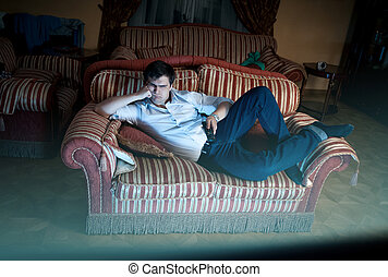 man lying on sofa and watching TV at night - Young man lying...