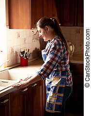 beautiful woman cleaning kitchen with cloth - Portrait of...