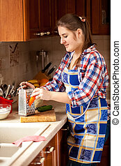 young woman grating carrot on kitchen - Portrait of young...