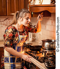 portrait of young housewife tasting soup from pan on fire -...
