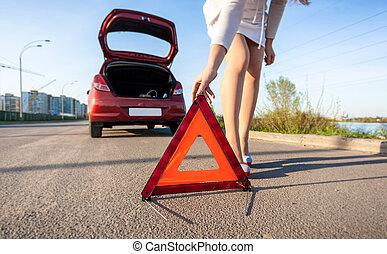 woman putting warning sign after car crash - Closeup photo...