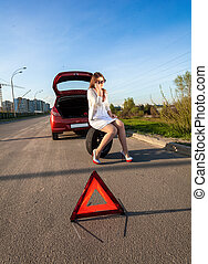 woman sitting on spare wheel against of broken car - Sexy...
