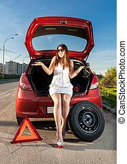 brunette woman sitting in trunk of broken car - Sexy...