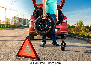 man holding spare wheel against broken car - Photo of man...