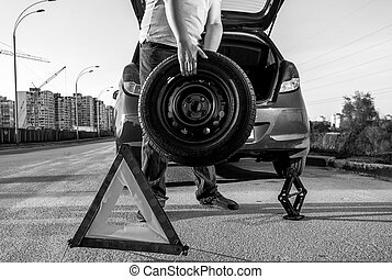 hoto of man carrying spare wheel against broken car - Black...