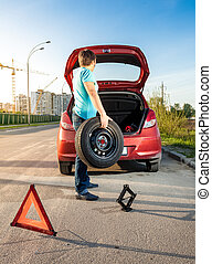 man taking spare wheel out of trunk - Photo of man taking...
