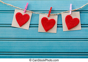 Hand-crafted felt hearts hanging with clothespins over blue...