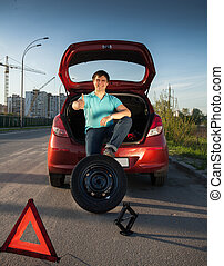 man sitting on car trunk and holding foot on spare wheel -...