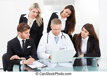 Doctor And Businesspeople Using Laptop - Male doctor and...