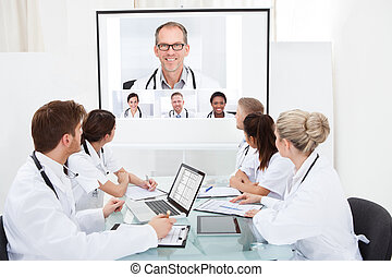 Team Of Doctors Looking At Projector Screen - Team of...