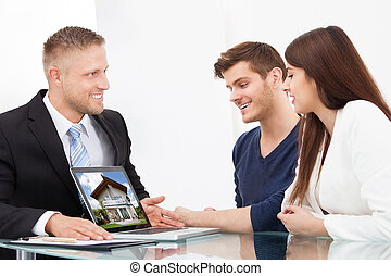 Businessman Showing House Picture To Couple On Laptop -...
