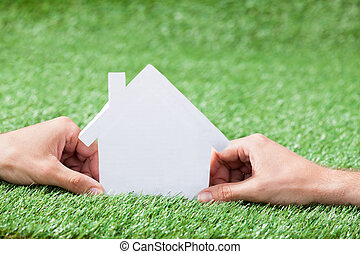 Hand Holding House Model In Green Field