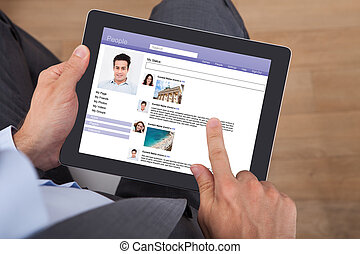 Businessman Surfing Social Networking Site On Digital Tablet...