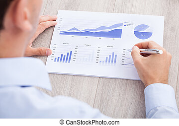 Businessman Analyzing Graph At Desk - Cropped image of...