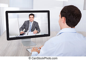 Businessman Video Conferencing With Coworker On Pc At Desk -...