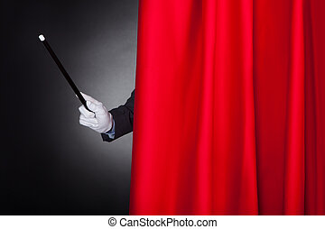 Magician Holding Wand Behind Stage Curtain - Cropped image...