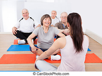 Trainer Training Customers In Yoga Class - Rear view of...