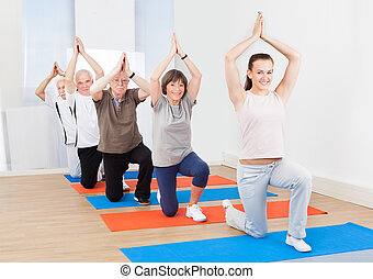 Trainer And Customers Practicing Yoga At Gym - Full length...