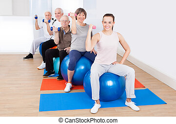 People Using Hand Weights While Sitting On Fitness Balls -...