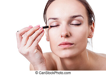 Woman using an eyeliner - Beautiful young woman using an...