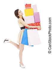 smiling young woman holding gift box and shopping bag