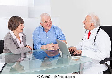 Senior Couple Discussing With Doctor - Happy senior couple...