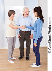 Caregiver Shaking Hands With Senior Couple - Young female...