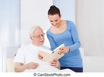 Caretaker And Senior Man Reading Book - Young female...
