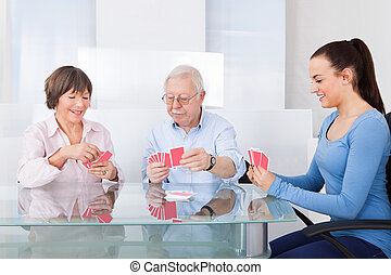 Caretaker Playing Cards With Senior Couple - Young female...