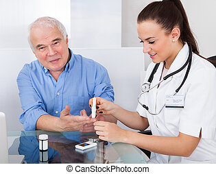 Doctor Using Lancelet On Senior Man