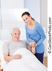 Portrait Of Happy Caregiver With Senior Man