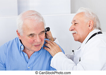 Doctor Examining Senior Man's Ear With Otoscope