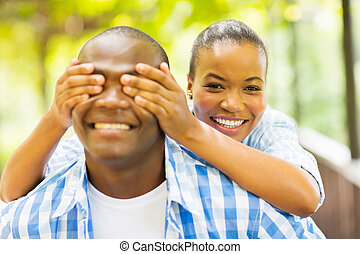 african girl covering boyfriend's eyes with hands