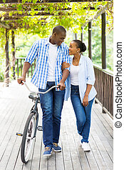 african american couple walking with bicycle