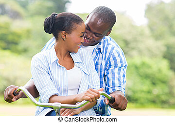 african couple riding a bike