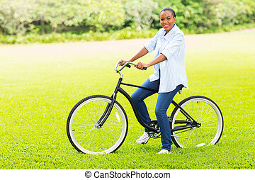 young adult african girl riding a bicycle