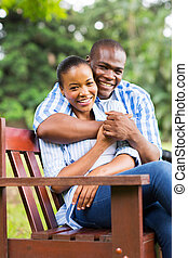 young african american couple sitting at the park -...