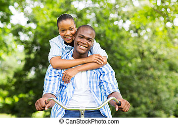 afro american couple riding a bike