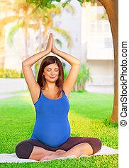 Pregnant girl meditating in the park